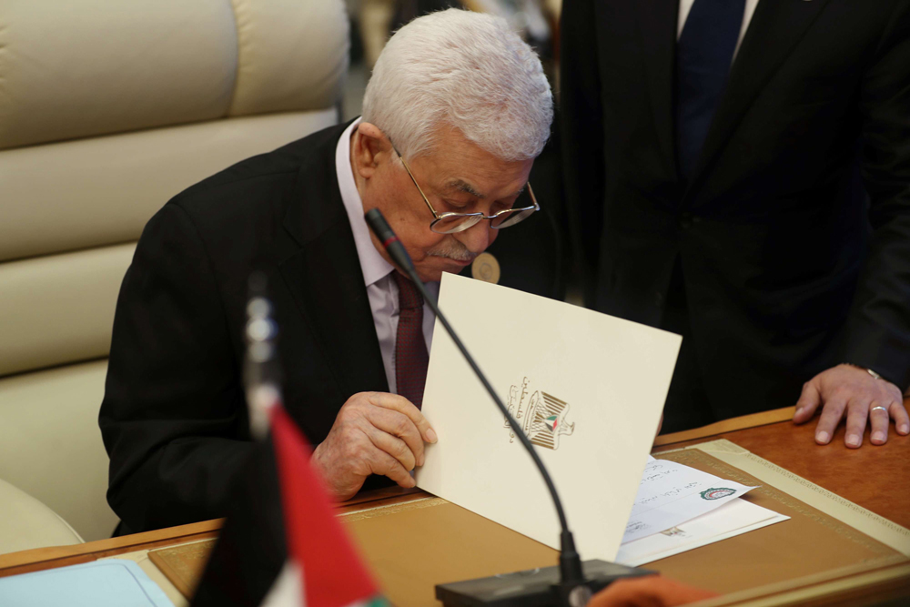 Squeezed out. Palestinian President Mahmoud Abbas reads a file during the Arab summit in Mecca, May 31.   (Reuters)