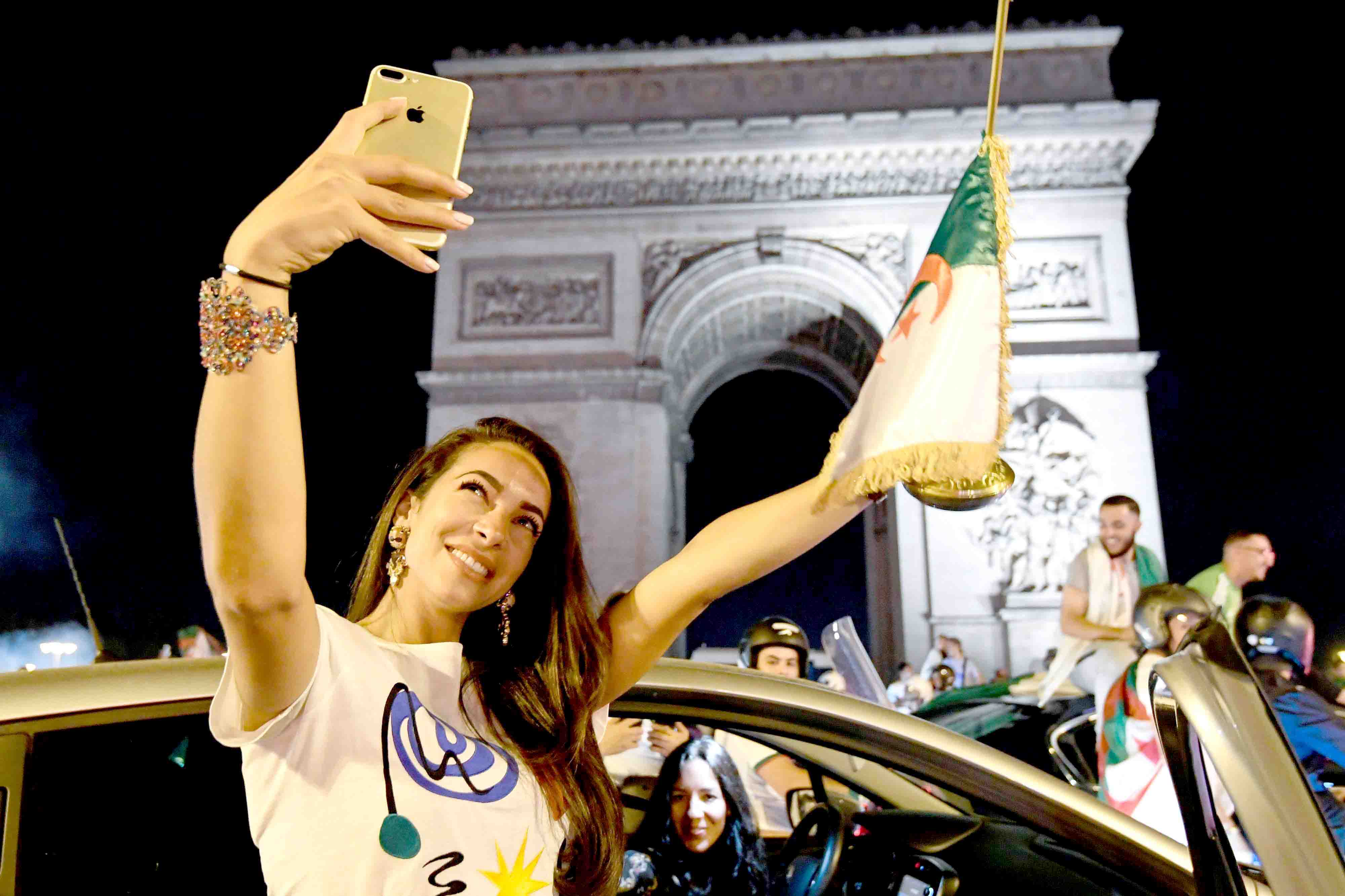 An Algerian supporter poses for a selfie with the Algerian national flag in front of the Arc de Triomphe as she celebrates on the Champs Elysees Avenue in Paris after Algeria won the 2019 Africa Cup of Nations final, July 19. (AFP)