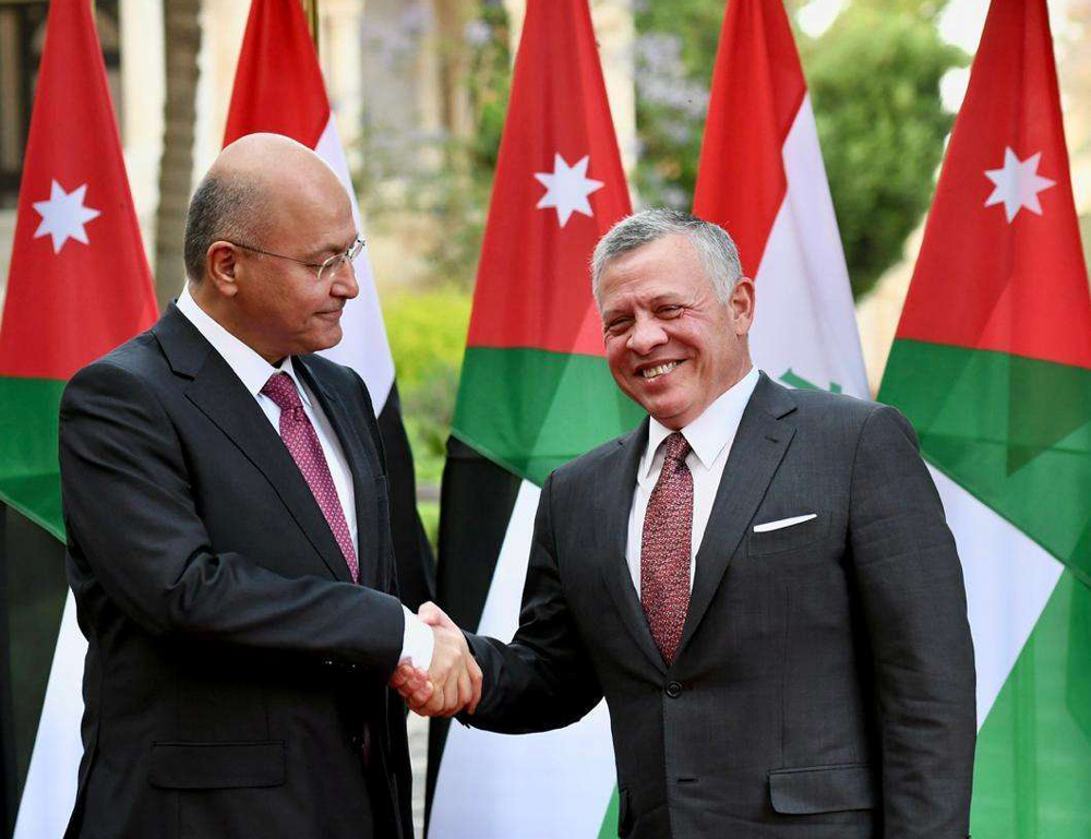 Iraqi President Barham Salih (L) and Jordanian King Abdullah II shake hands during a welcoming ceremony in Amman, last May. (Reuters)