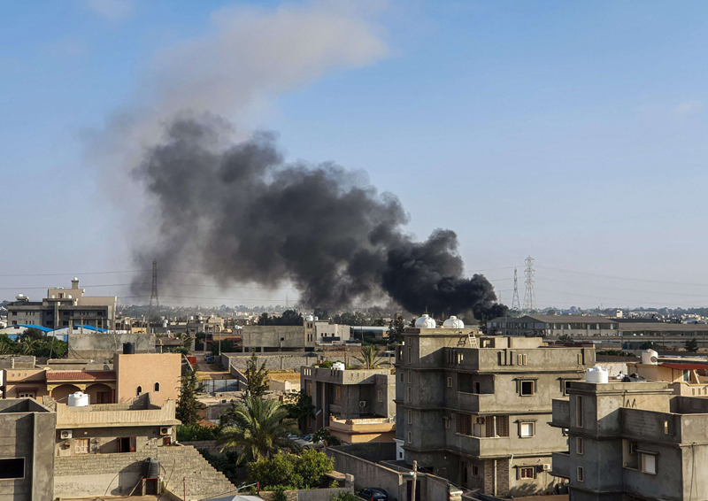 Sitting on a powder keg. Smoke plumes rise in Tajoura, south of Tripoli, June 29.  (AFP)
