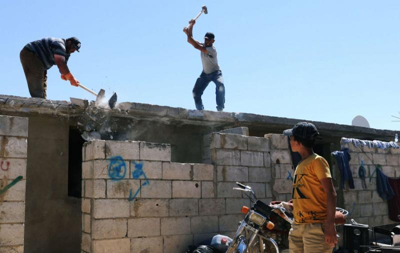 Workers dismantle concrete huts at a makeshift Syrian refugee camp in the Lebanese town of Arsal, July 4. (Reuters)