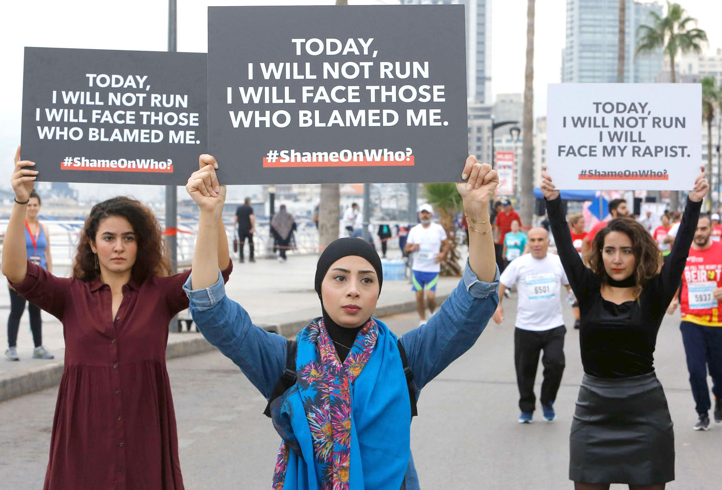 Protesters hold banners with messages against sexual assault during the Beirut Marathon, last year. (AFP)