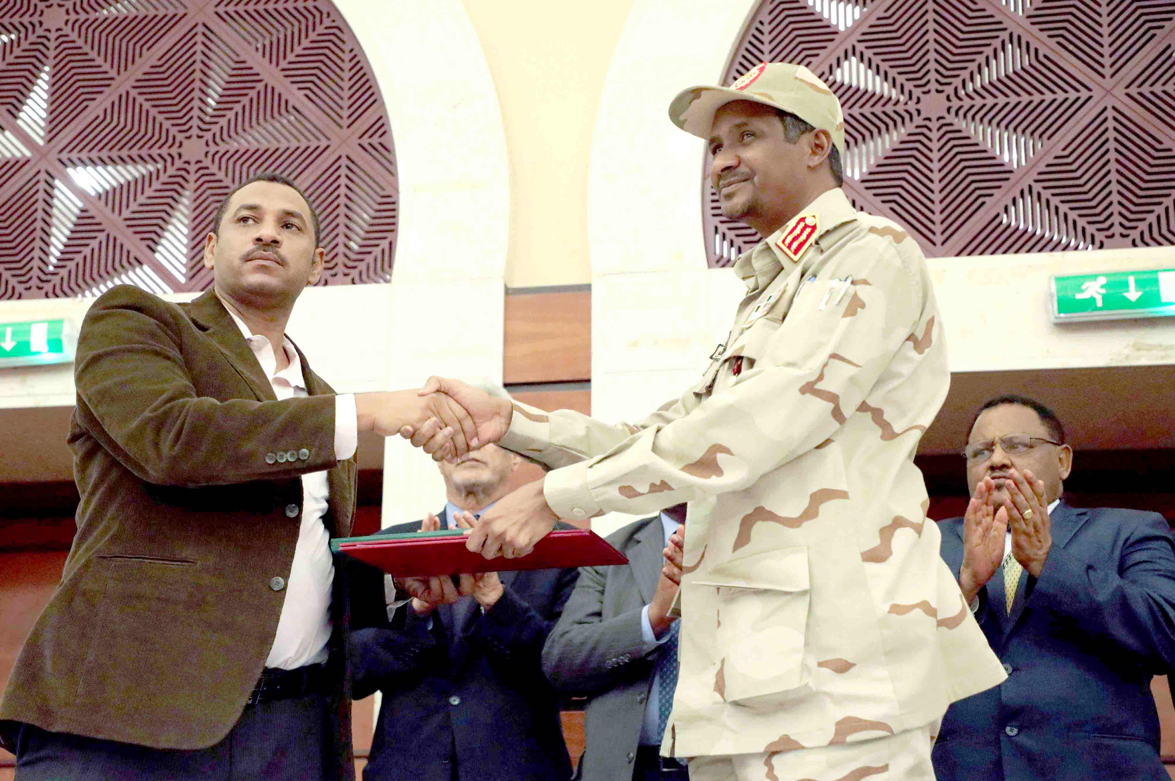 Deputy Head of Sudanese Transitional Military Council Mohamed Hamdan Dagalo and opposition alliance coalition's leader Ahmad al-Rabiah shake hands after signing a political accord in Khartoum, July 17. (Reuters)
