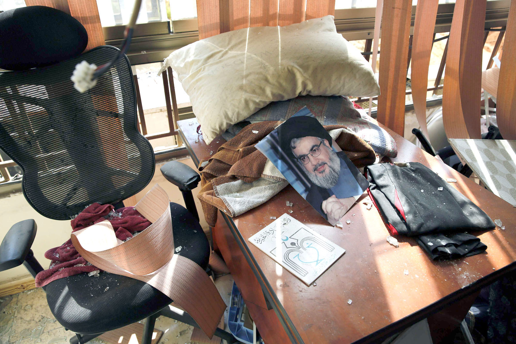 Closer to the brink than ever. A picture of Hezbollah leader Sayyed Hassan Nasrallah lies amid damage inside the Lebanese Hezbollah media office in a southern suburb of Beirut, August 25.        (AP)