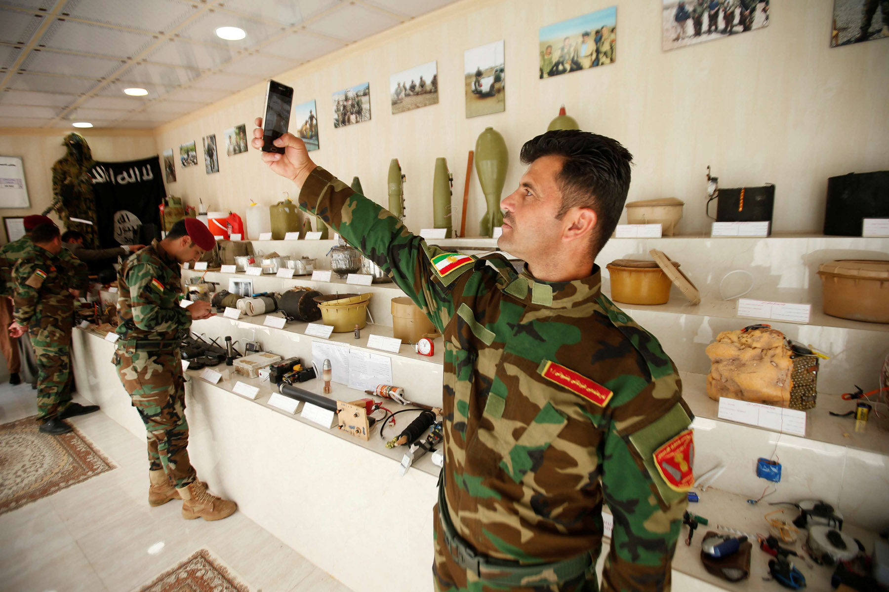 Unfinished history. A member of Kurdish Peshmerga military forces takes a selfie next to explosives and items that were used by ISIS militants, at a museum in Erbil. (Reuters)