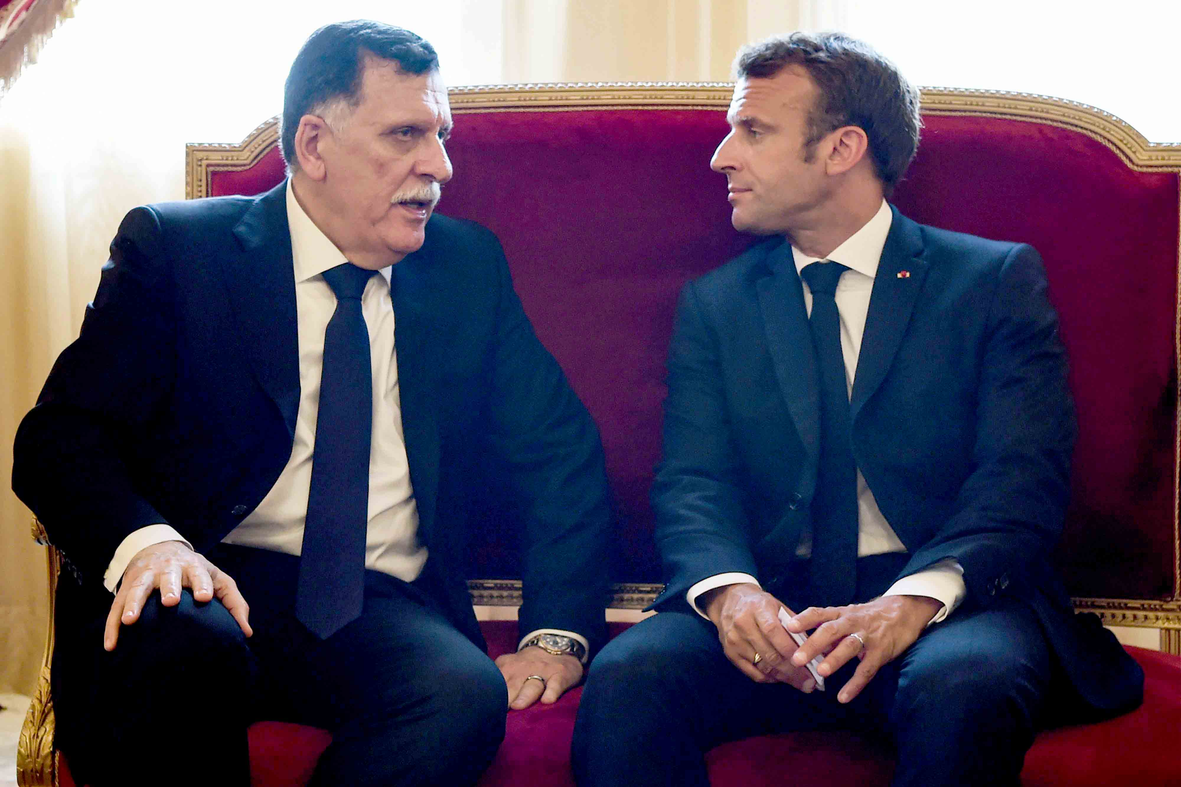 French President Emmanuel Macron (R) speaks with Libya's UN-recognised Prime Minister Fayez al-Sarraj in Tunis, July 27. (AFP)