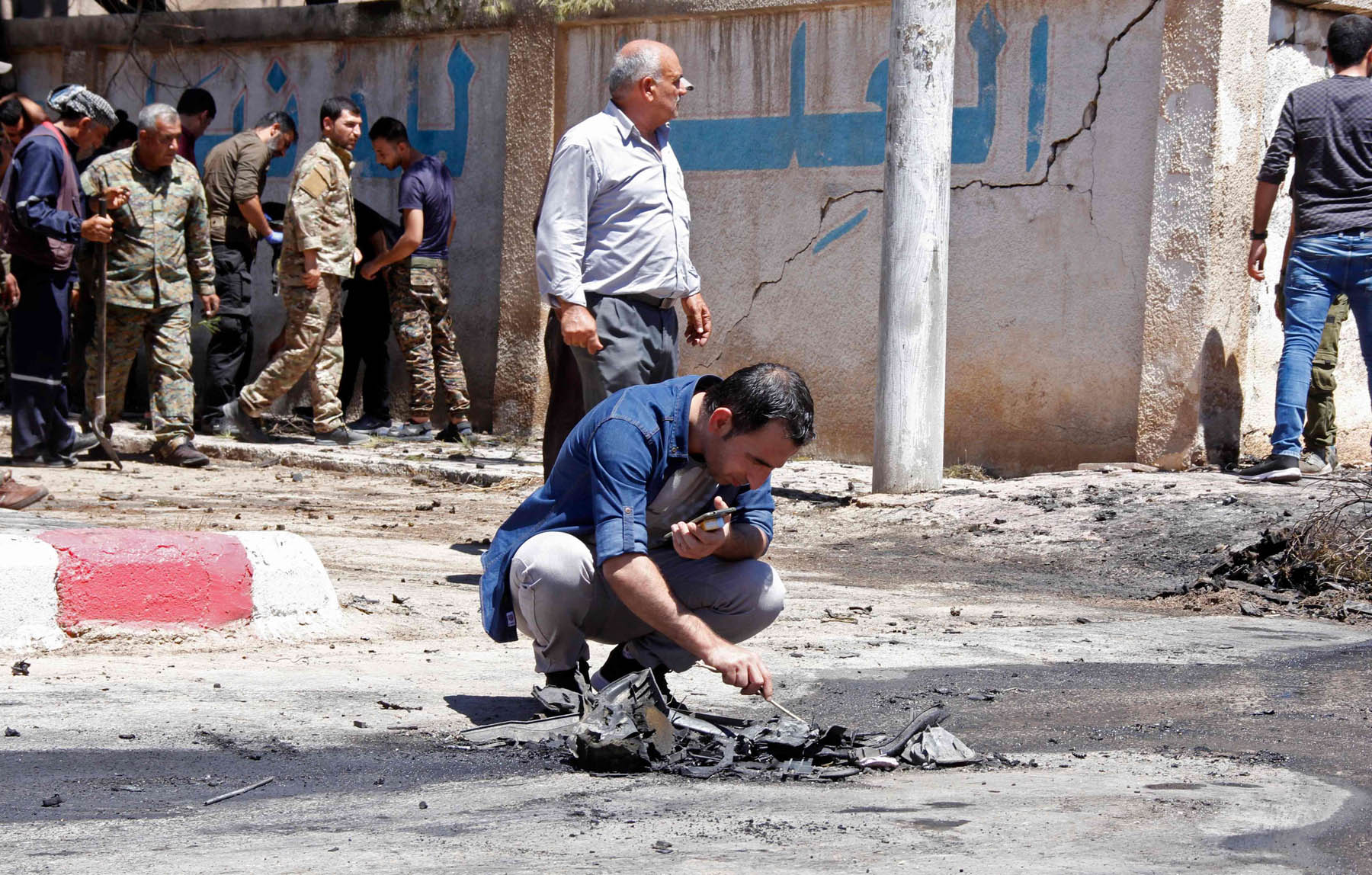 A member of the Kurdish security forces examines debris at the site of an ISIS-claimed car bombing in the town of al-Qahtaniyah in the Hasakah province, August 7. (AFP)