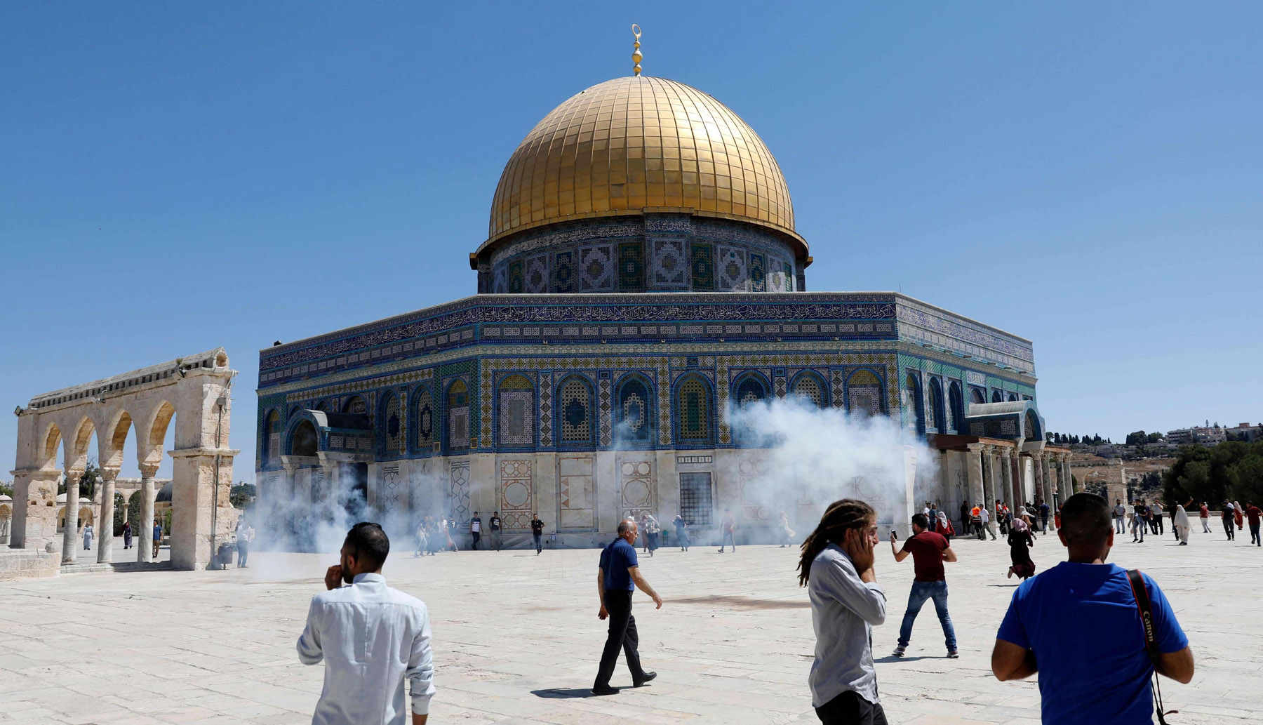 Palestinians run for cover from sound grenades fired by Israeli security forces outside the Dome of the Rock mosque in Jerusalem's Al-Aqsa Mosque compound, August 11. (AFP)