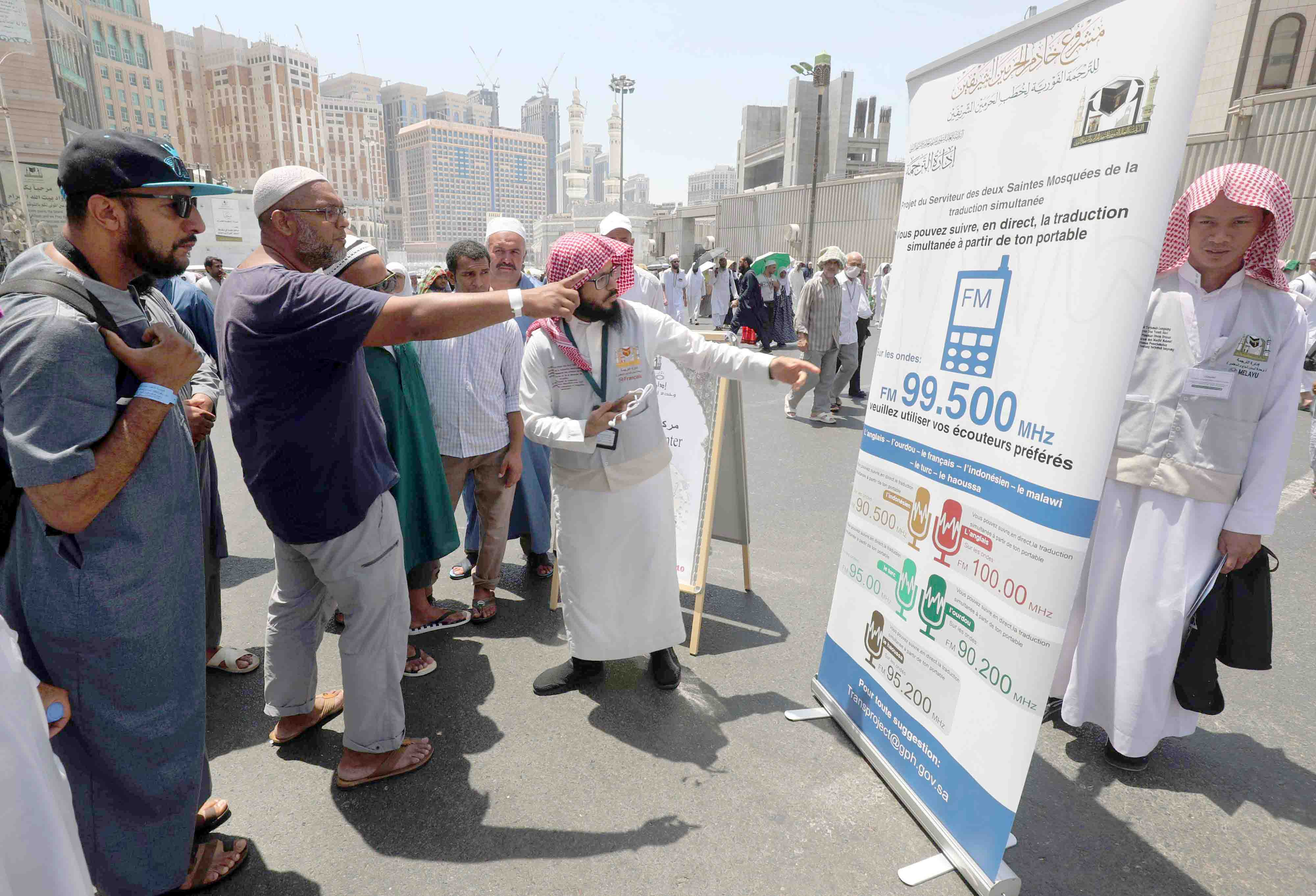 A translator helps pilgrims find information on a poster displaying helpful smartphone applications in Mecca, August 18.(AFP)