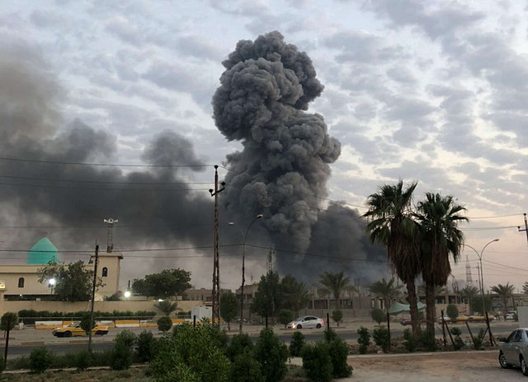 Plumes of smoke rise after an explosion at a military base south-west of Baghdad, August 12. (AP)