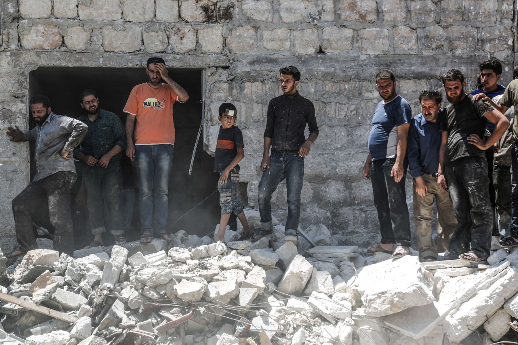 Syrians stands at a site of a reported air strike Maarat al-Numaan, last July. (DPA)