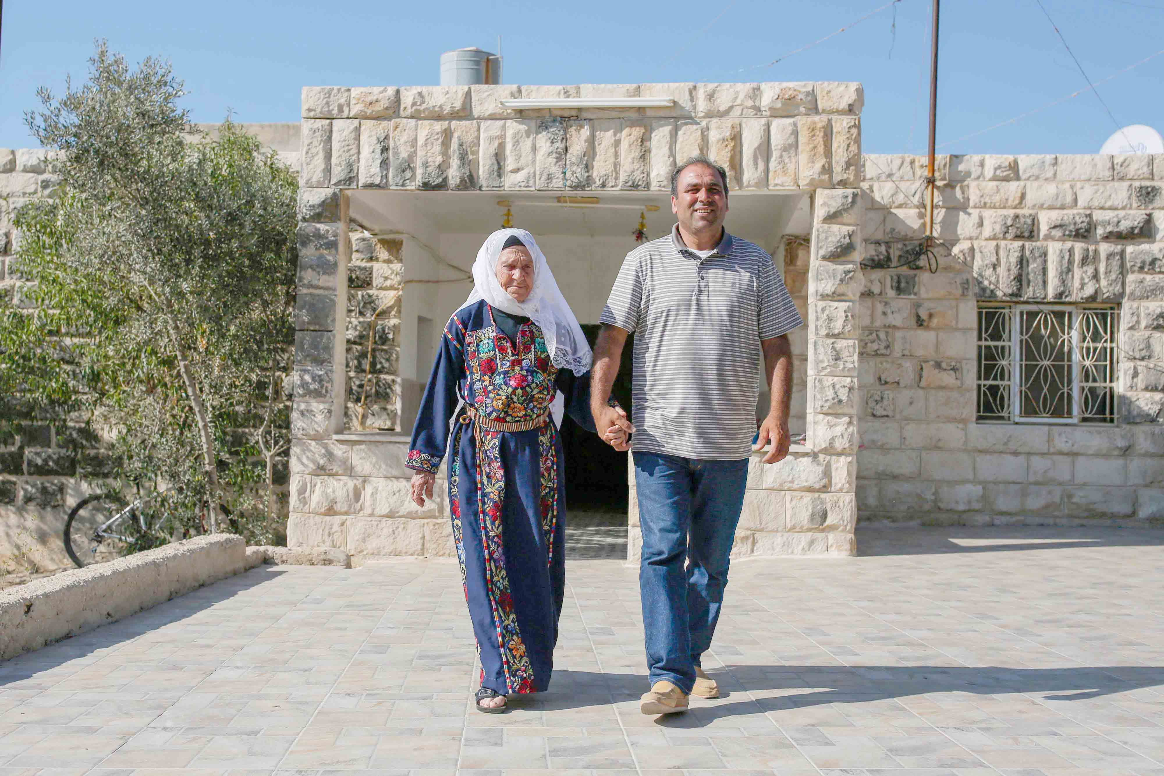 Muftia Tlaib, the maternal grandmother of US Representative Rashida Tlaib, walks with her son Bassam (R) outside their home in the village of Beit Ur al-Fauqa in the occupied West Bank, August 15.(AFP)