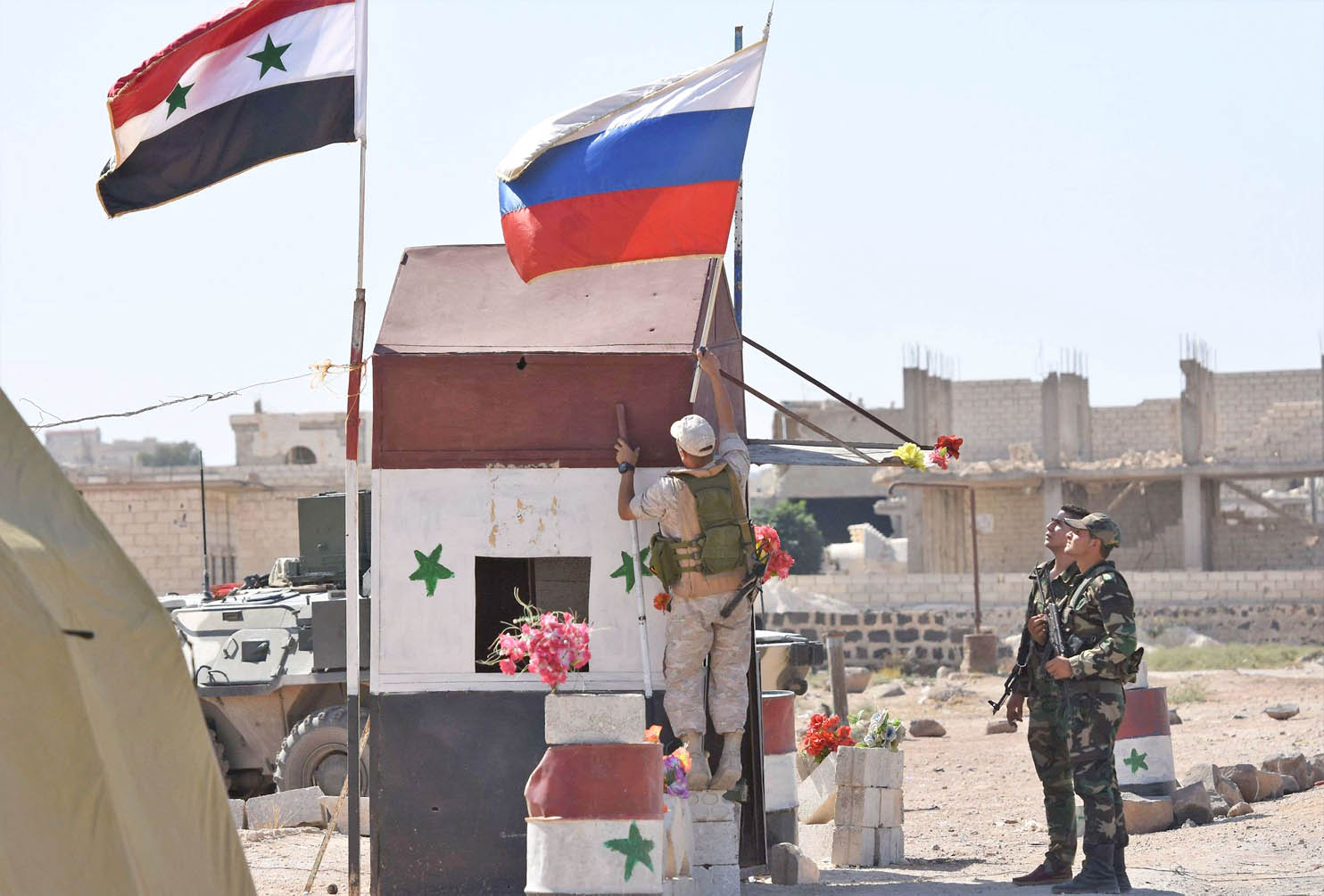 A Russian soldier places the national flag at the Abu Duhur crossing on the eastern edge of Idlib. (AFP)