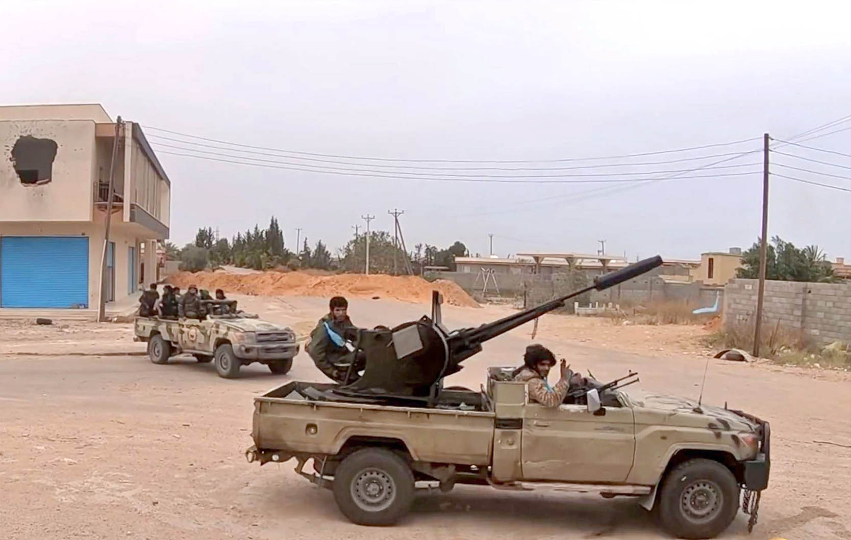 A file picture shows LNA fighters advancing on a road south of Tripoli. (AFP)
