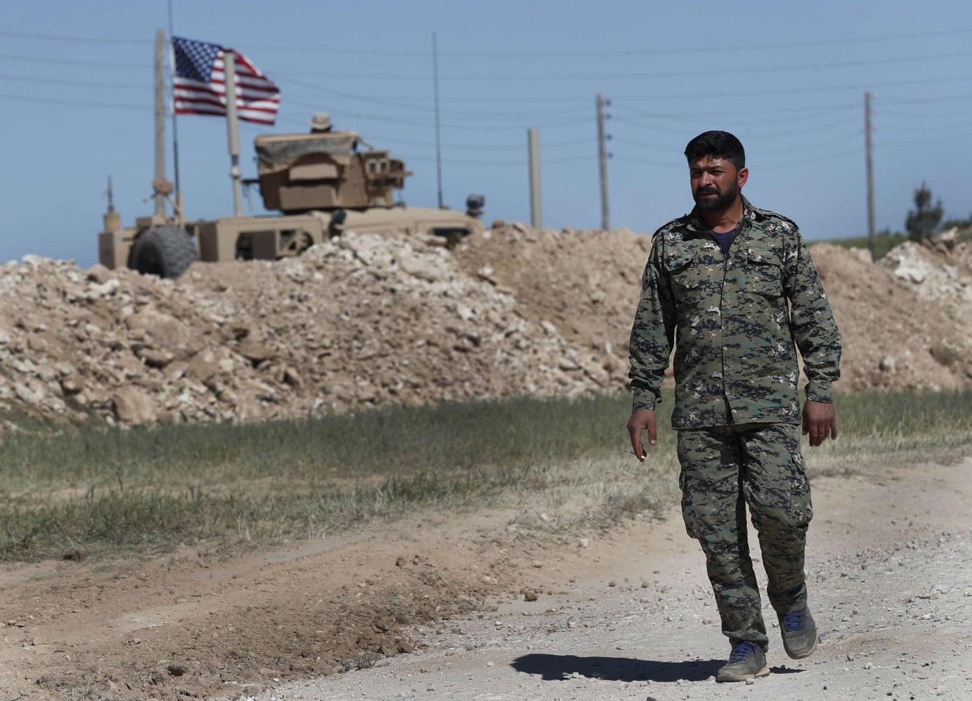 U.S-backed Syrian Manbij Military Council soldier passes a U.S. position near the tense front line with Turkish-backed fighters, in Manbij, north Syria, April 4, 2018. (AP)