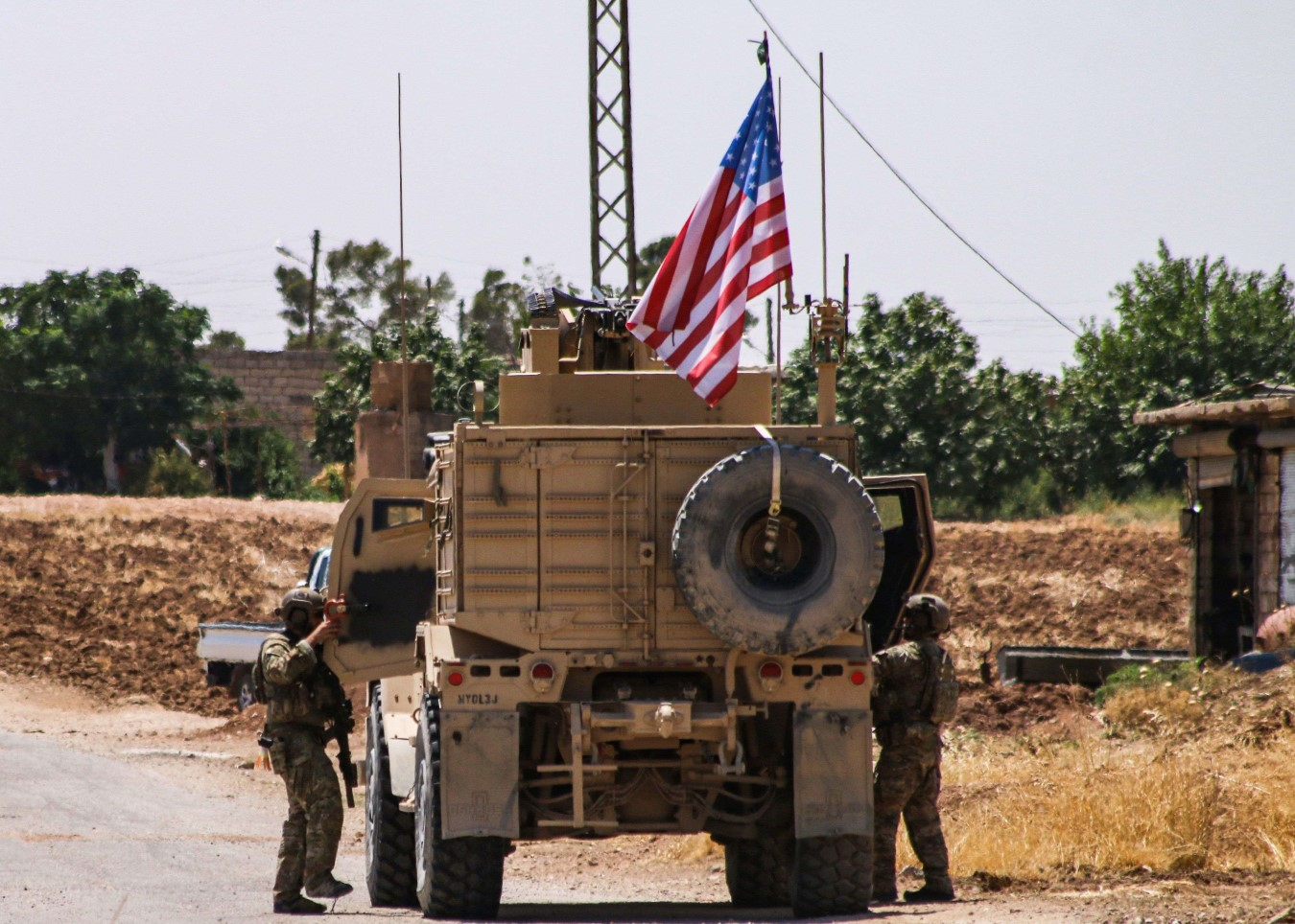 US soldiers climb into a vehicle of the US-led coalition as they prepare to leave the city of Ras al-Ain in Syria's Hasakeh province, July 28. (AFP)