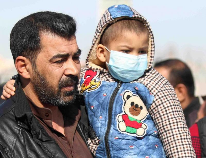 An Iraqi man carries his sick child during a demonstration outside a children's hospital in Basra to demand the delivery of medical supplies for cancer patients. (AFP)