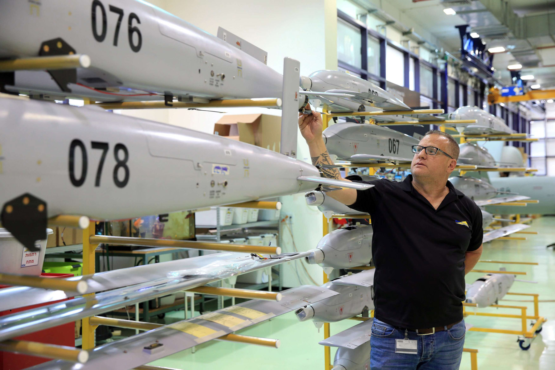 Advanced capabilities. An employee stands next to unmanned aerial vehicles (UAVs) at the Elbit Systems Ltd. drone factory in Rehovot, Israel.  (Reuters)
