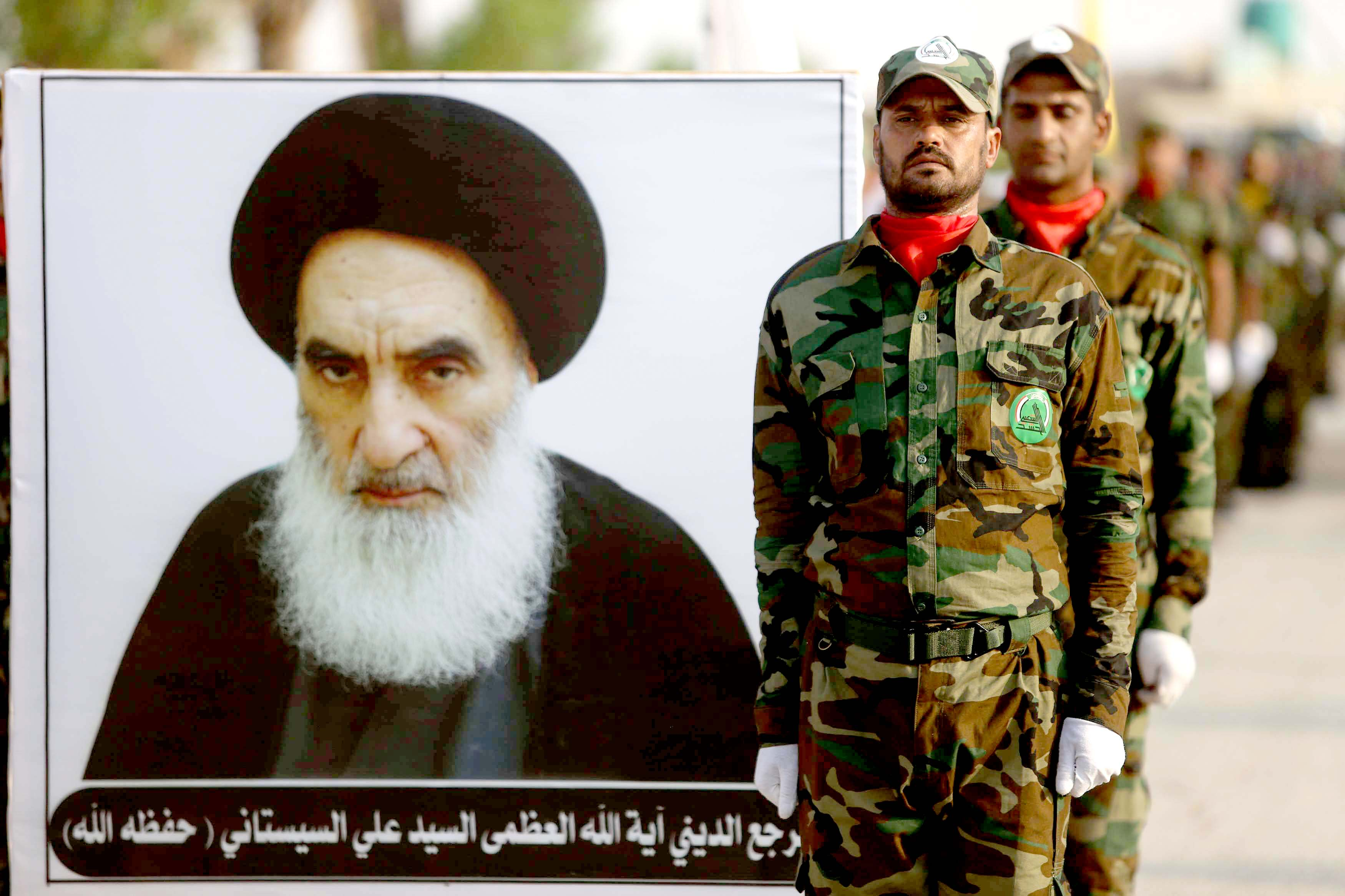 Easily offended. Members of Iran-backed Shia Popular Mobilisation Forces at a training centre in Karbala carry a placard with an image of Iraqi Grand Ayatollah Ali al-Sistani, August 30. (AFP)