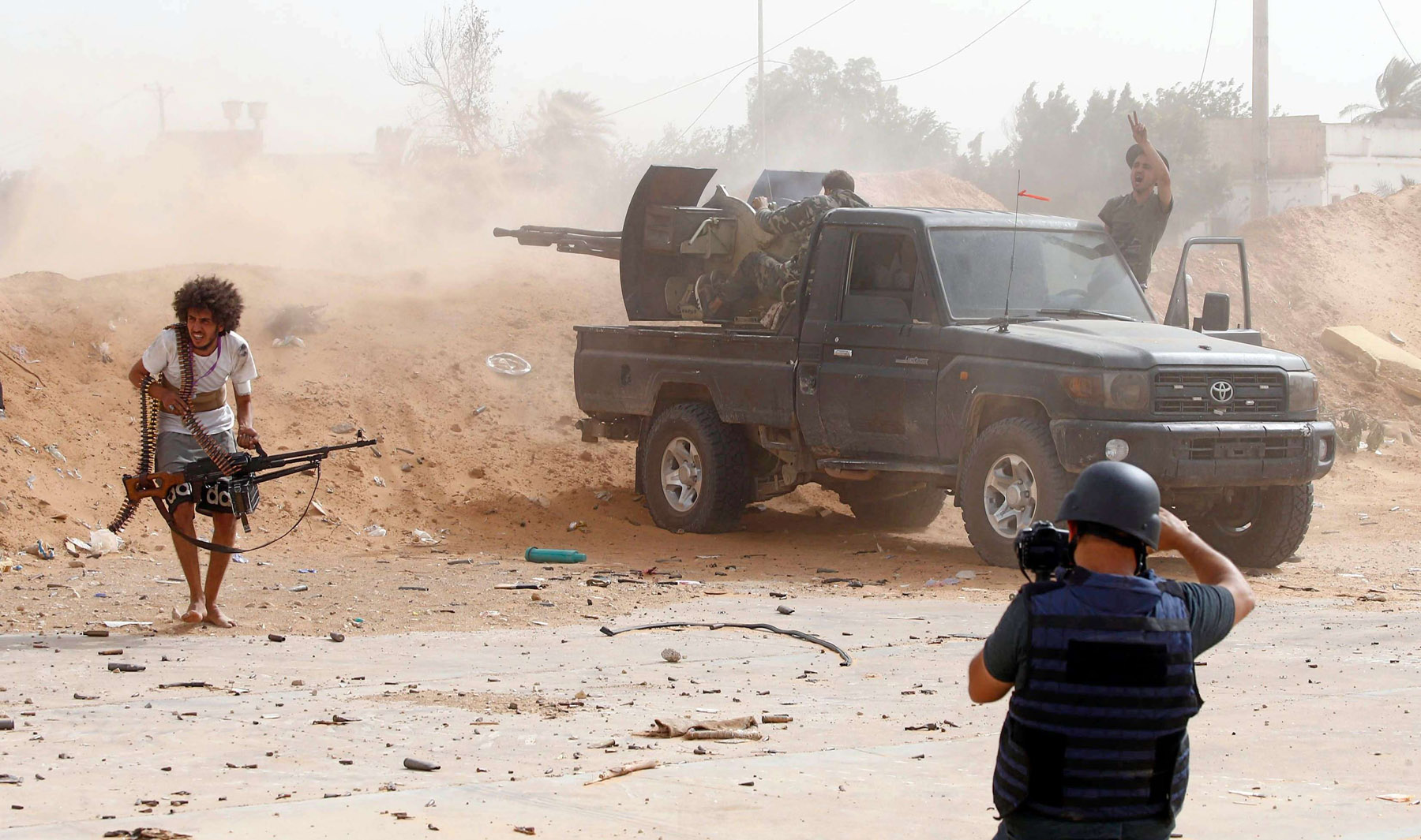 A journalist reports from the front line during clashes between LNA forces and fighters loyal to the Libyan government of Fayez Sarraj, south of Tripoli. (AFP)
