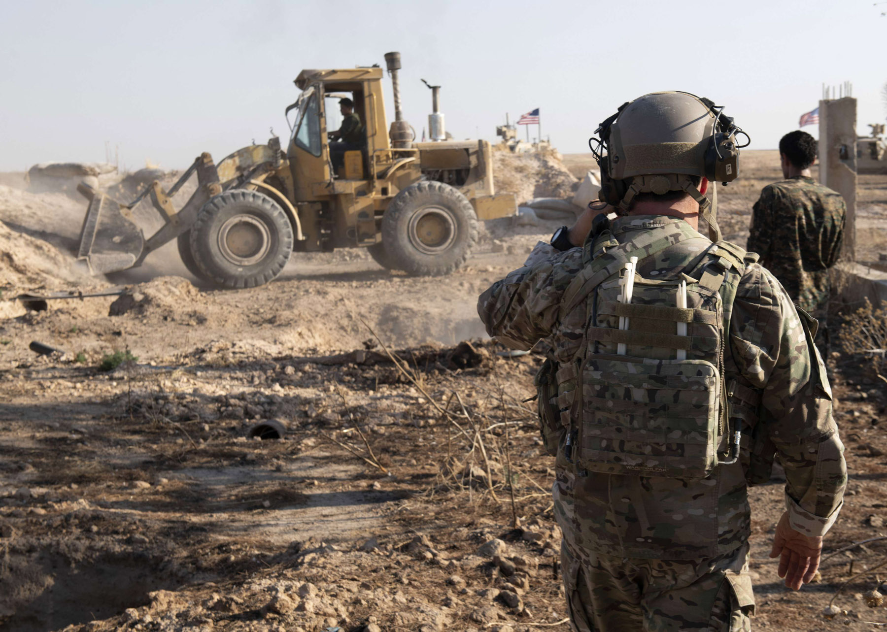 A US soldier watches as Syrian Democratic Forces remove military fortifications during the implementation of the security mechanism along the Turkey-Syria border in north-eastern Syria, August 22. (AP)