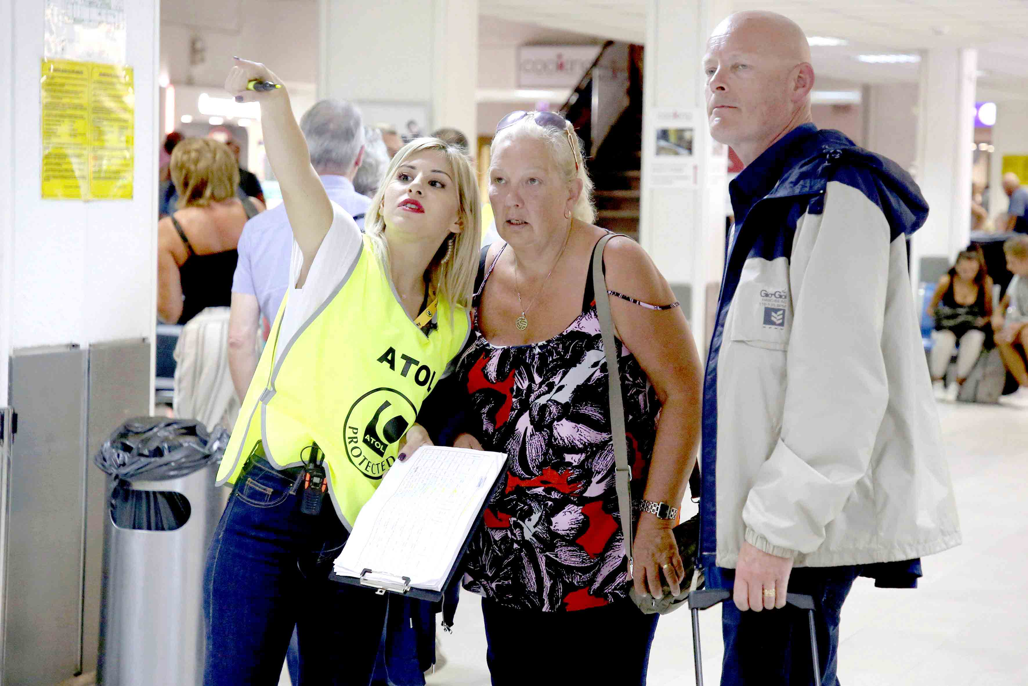 A long odyssey comes to abrupt end. An Air Travel Organiser's Licence official directs Thomas Cook customers at the airport of Heraklion, on the island of Crete, Greece, September 24.(Reuters)