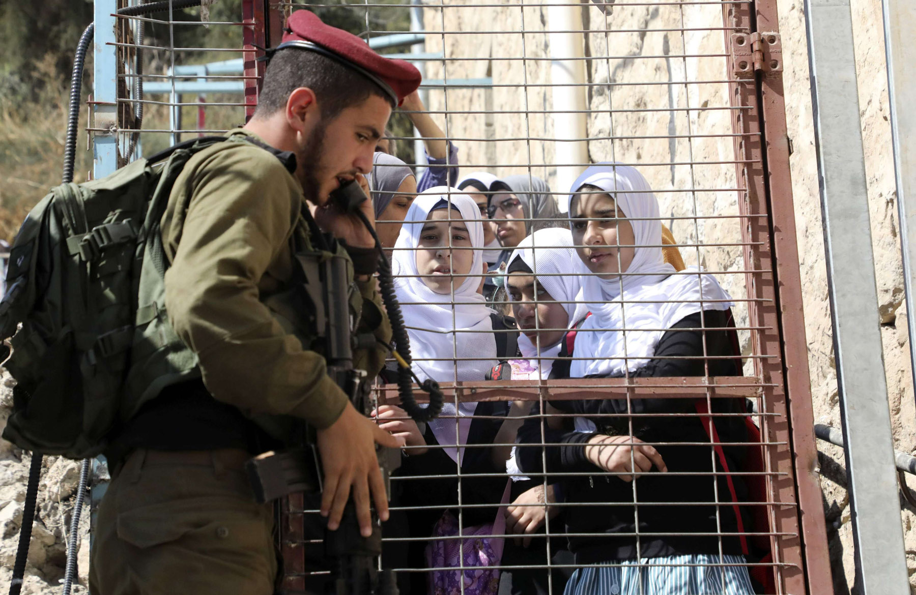 Palestinian pupils and teachers wait by a closed iron gate as an Israeli soldier gets an authorisation to open it near al-Shuhada street in the West Bank town of Hebron, September 4. (AFP)