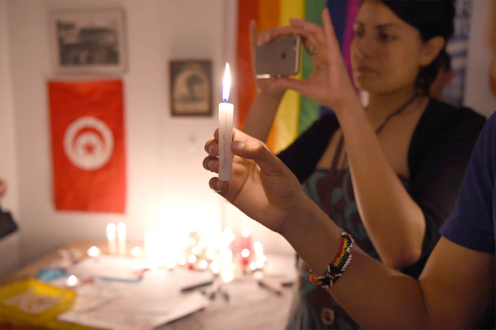 A rainbow flag and a Tunisian national flag hang in the background as activists light candles during an LGBT event in Tunis. (AFP)