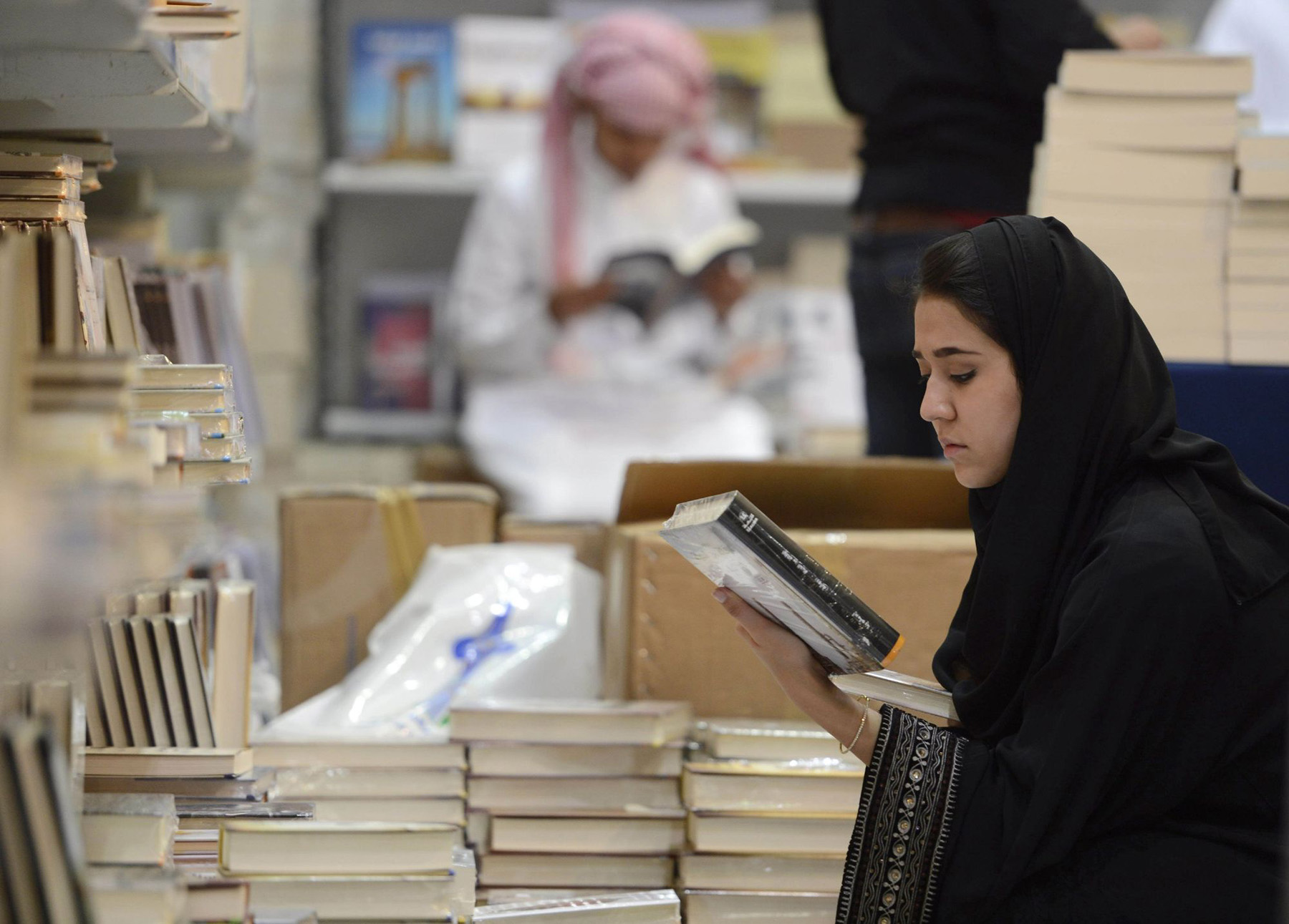 A woman looks at a book during the Riyadh Book Fair at the International Exhibition Centre in Riyadh. (Reuters)
