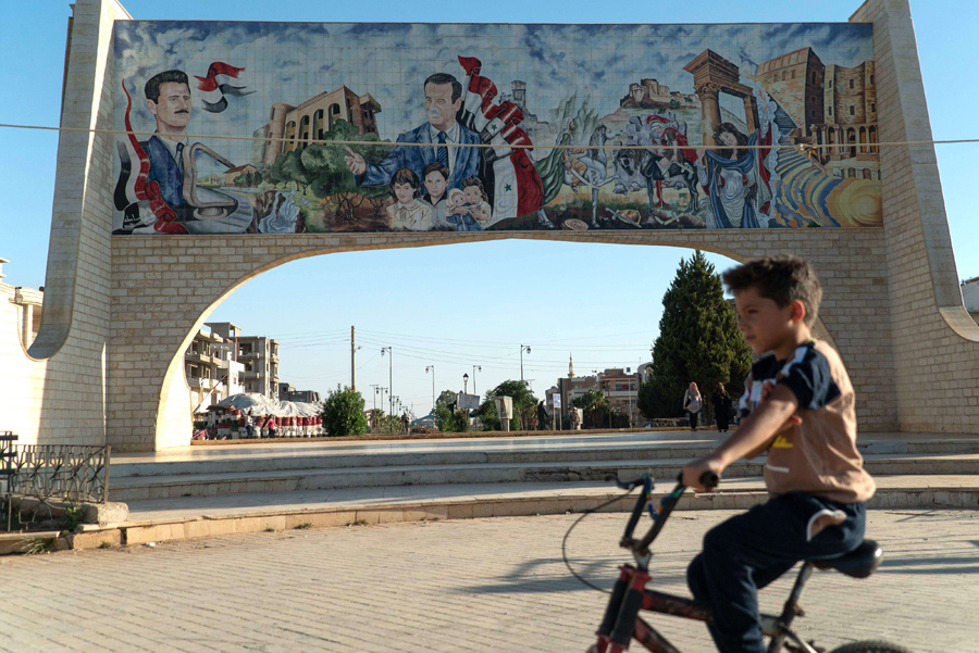 A boy rides a bicycle in front of a gate bearing images of Syrian President Bashar Assad (L) and his late father Hafez Assad in the southern Syrian city of Daraa, 2018. (AFP)