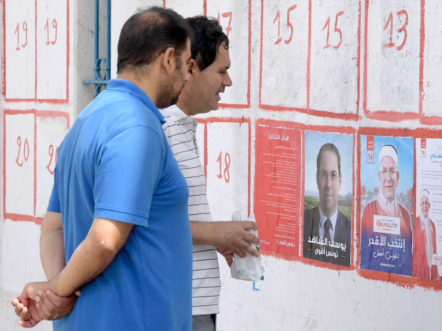 Tunisians look at posters of presidential candidates in Tunis. (AFP)