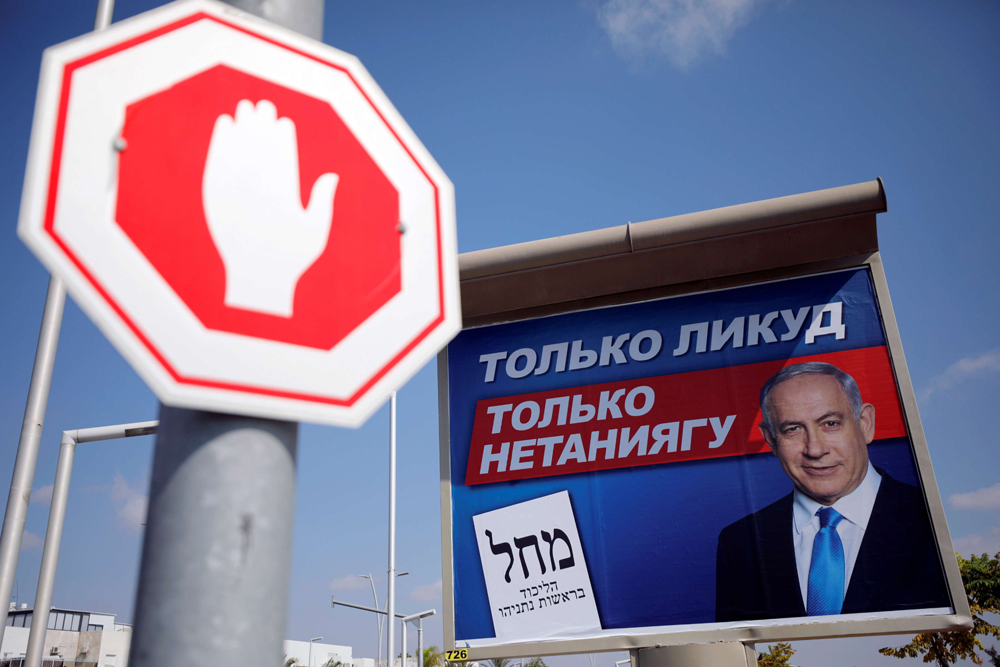 A Likud party election campaign banner with Russian writing in seen near a road sign in Ashdod, Israel September 9. (Reuters)