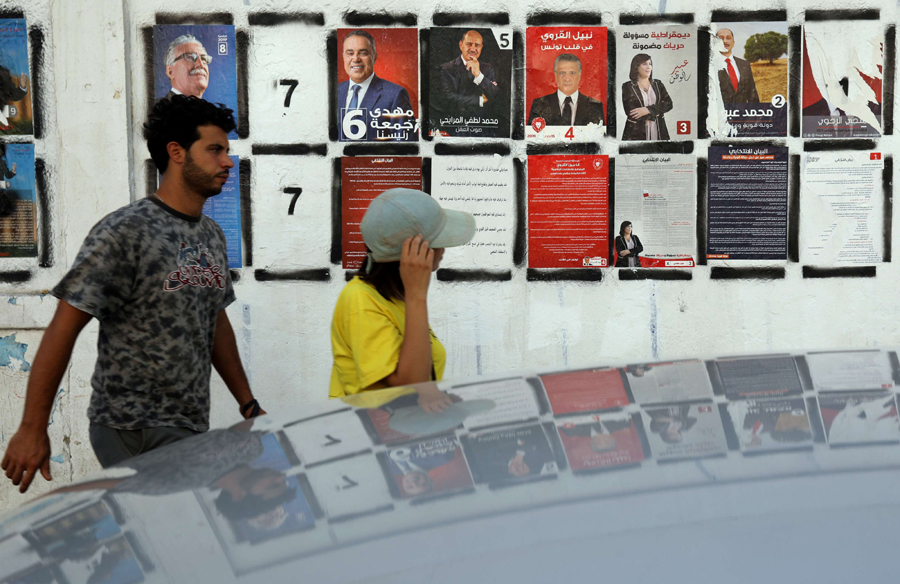 People walk past Tunisian election campaign posters for presidential candidates in Tunis, September 13. (Reuters)