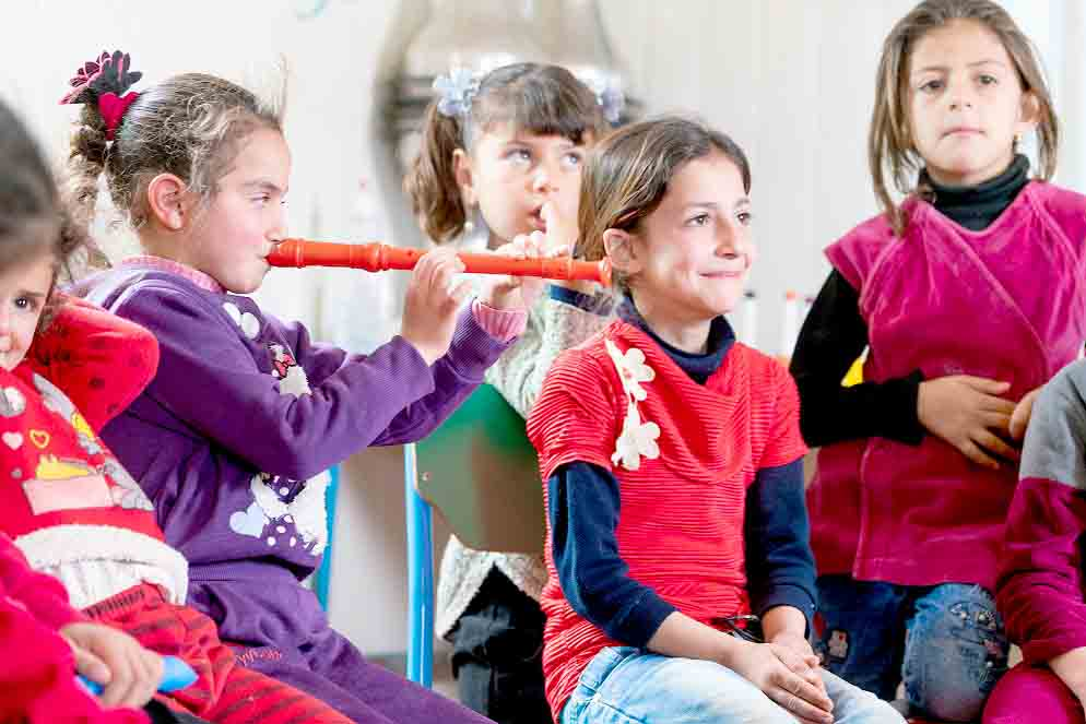 "Young Syrian refugees enjoy a session of UNICEF's ""My Music"" initiative. (UNICEF)"