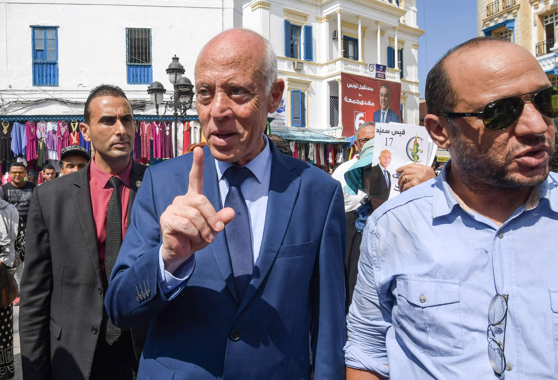 Kais Said, a Tunisian presidential candidate, speaks with people during an electoral campaign tour at an outdoor market in the capital Tunis on September 10. (AFP)