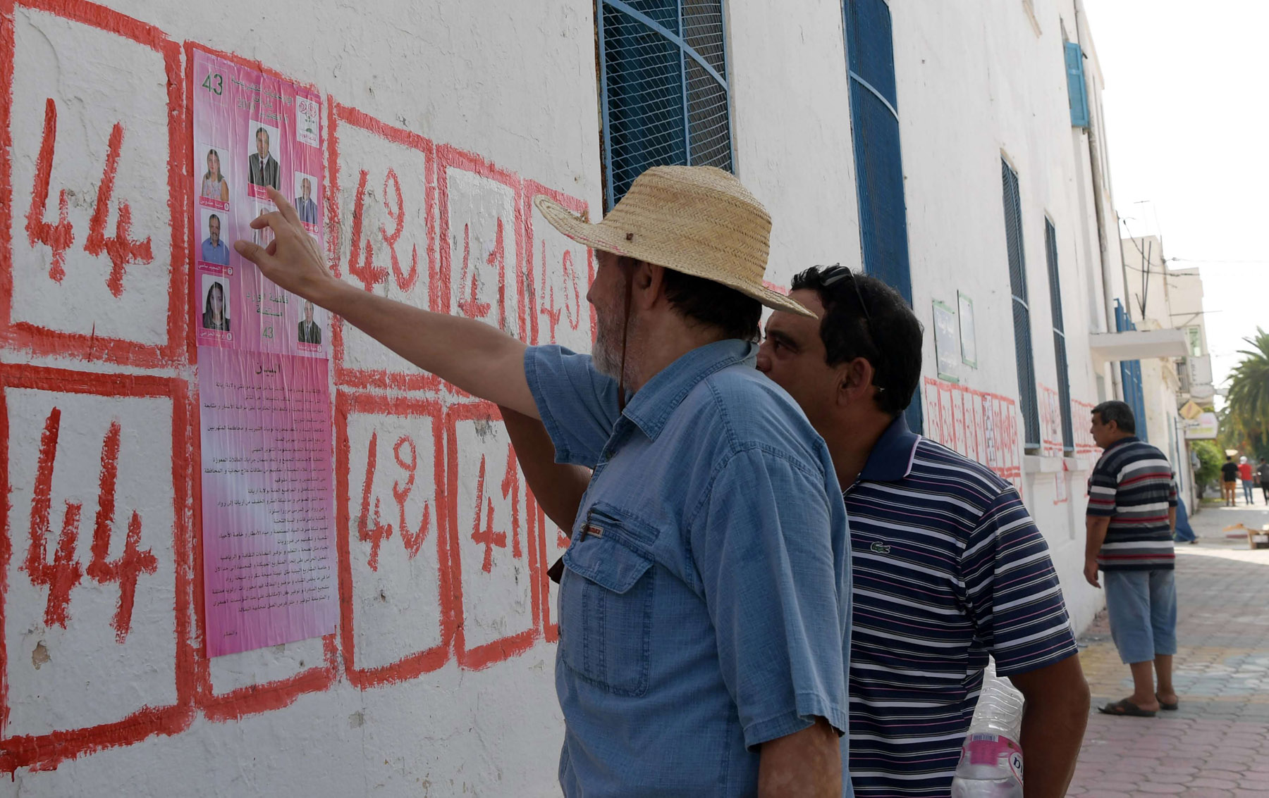 Tunisians consult lists of candidates for the upcoming legislative elections in Tunis. (AFP)
