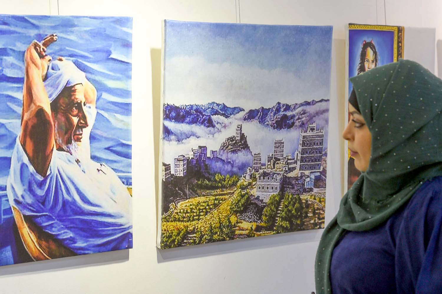 "A message of life. A visitor looks at paintings on display at the ""Yemeni Art Caravan"" exhibition in Giza, Egypt.(Al Arab)"