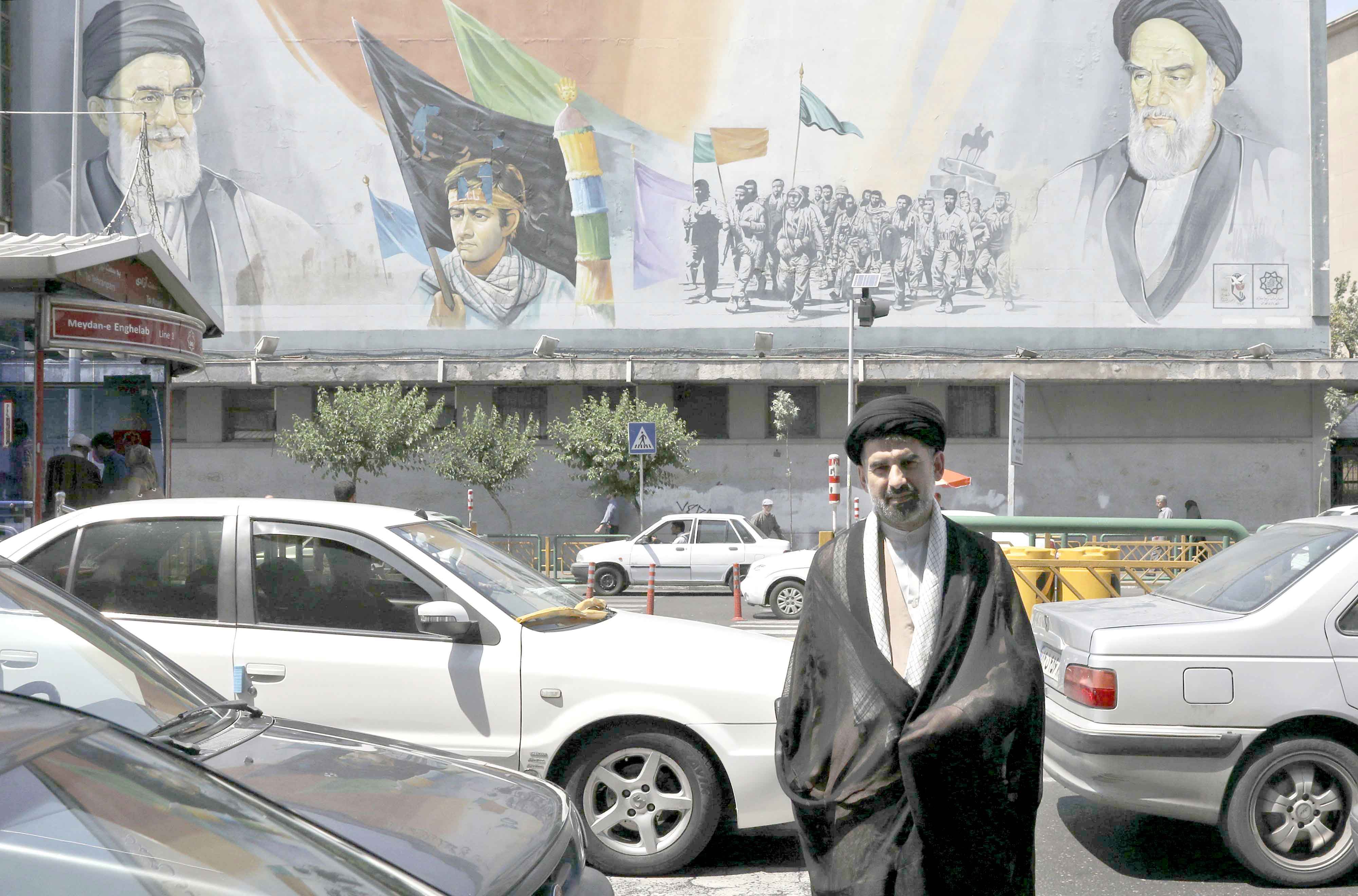 At a crossroads. A cleric crosses a street in front of a mural depicting late Iranian founder of the Islamic Republic Ayatollah Khomeini (R) and Supreme Leader Ayatollah Ali Khamenei (L) in downtown Tehran.(AP)