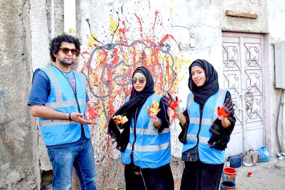 Promoting diversity. Young Saudis pose in front of a painted wall in an old neighbourhood in Jeddah.  (Al Arab)