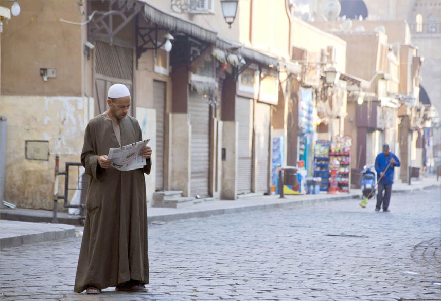 More than just news. An Egyptian man reads a newspaper in the neighbourhood of El-Gamaliah in Cairo. (AP)