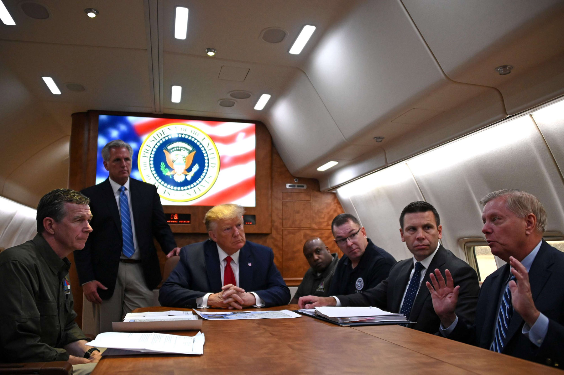 US President Donald Trump holds a meeting aboard Air Force One with North Carolina Governor Roy Cooper (L), House Minority Leader Kevin McCarthy (standing), Acting Secretary of Homeland Security Kevin McAleenan (2nd R), and US Senator Lindsey Graham, among others, September 9. (AFP)