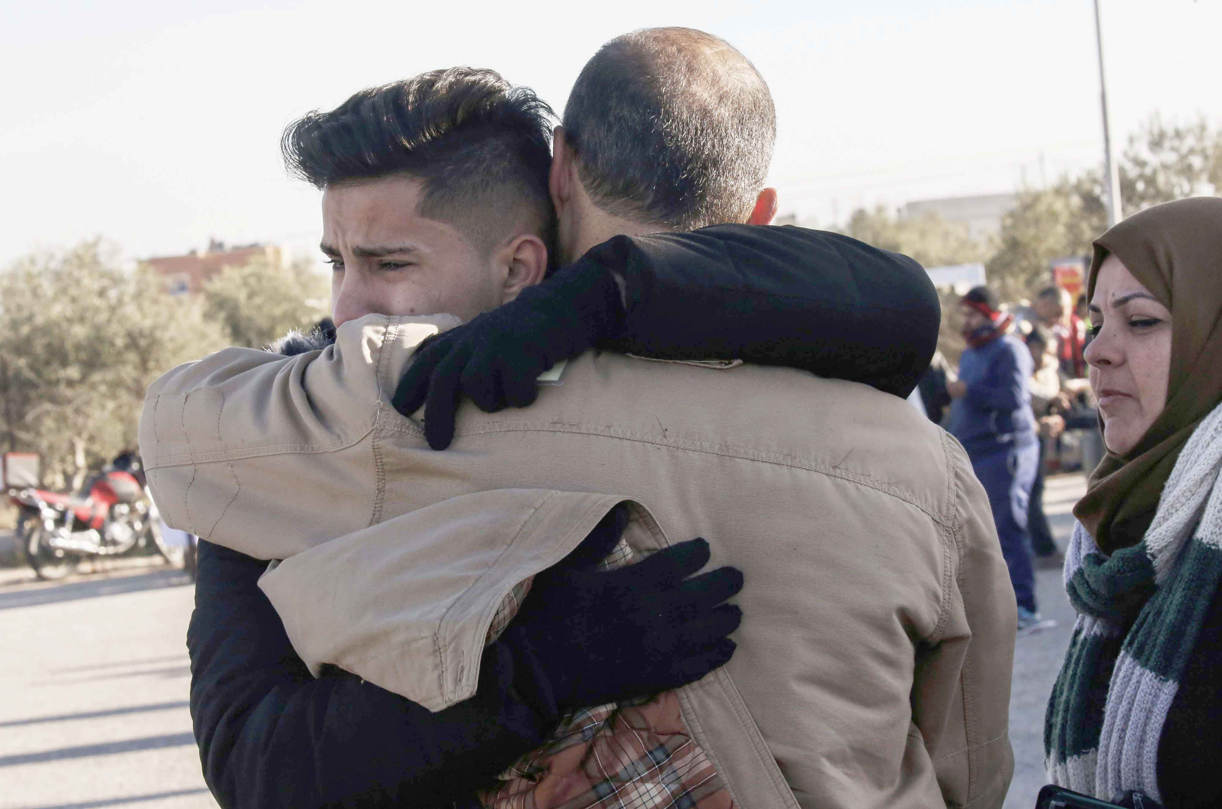 A Palestinian hugs a family member as he prepares to cross to Egypt through the Rafah border crossing in the southern Gaza Strip. (AFP)