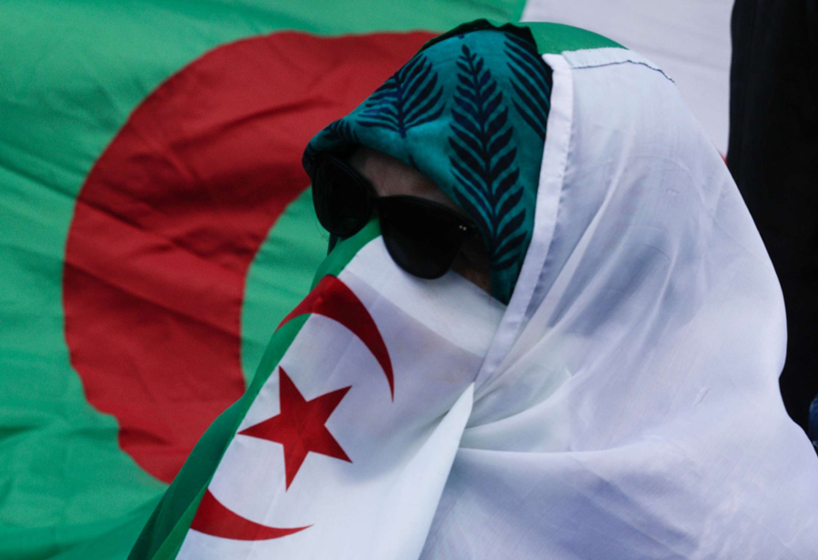 A woman wears an Algerian flag during a protest over fears of plot to prolong the Algerian president's rule, in Paris, March 17. (AFP)