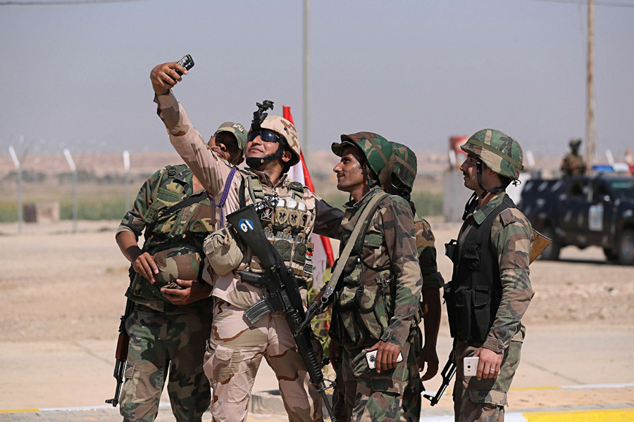 Dominating with ease. Iraqi and Syrian security forces take a picture during the opening ceremony of the crossing between the Iraqi town of Qaim and Syria's Albukamal, September 30. (AP)