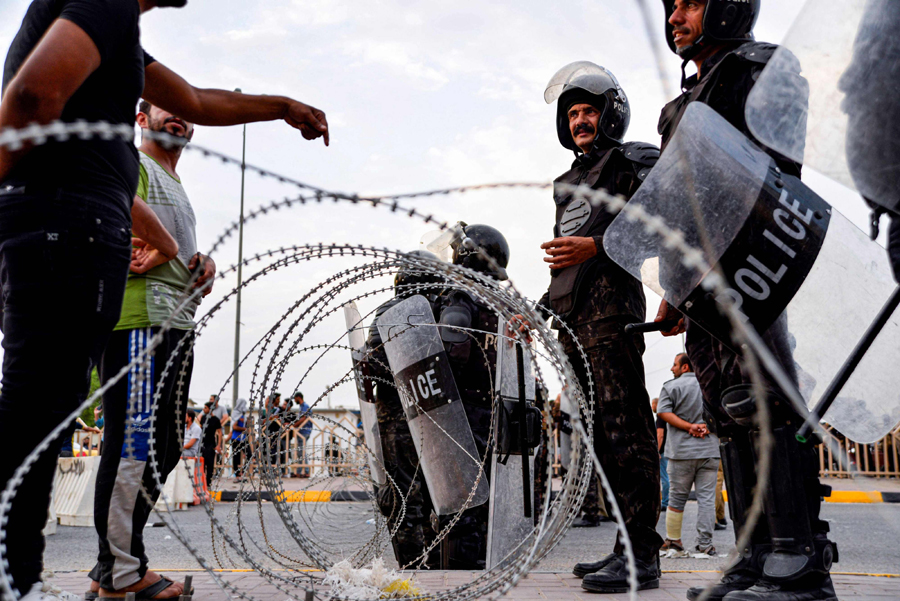 Protesters speak with Iraqi riot police members behind barbed wire barricades during a demonstration in the central Iraqi shrine city of Najaf on October 1, 2019. AFP