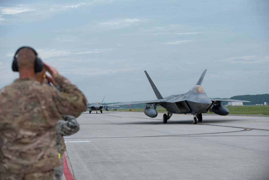 Away from base. F-22 Raptors taxis prepare to take off at Al Udeid Air Base in Qatar. (Reuters)