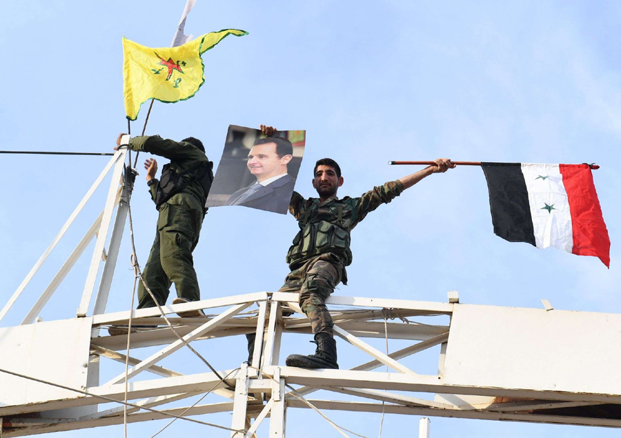 A Syrian regime soldier holds up a portrait of President Bashar al-Assad as he waves a Syrian national flag while another stands by a Kurdish People's Protection Units (YPG) yellow flag, in the Syrian town of Kobane (Ain al-Arab), October 18. (AFP)