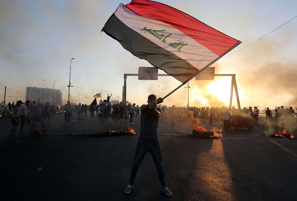 An Iraqi protester waves the national flag during a demonstration against state corruption, failing public services and unemployment, in Baghdad, October 5. (AFP)