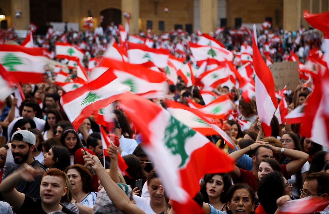 Lebanese demonstrators wave national flags during a demonstration against the government, on the 10th day of protests across Lebanon. (dpa)