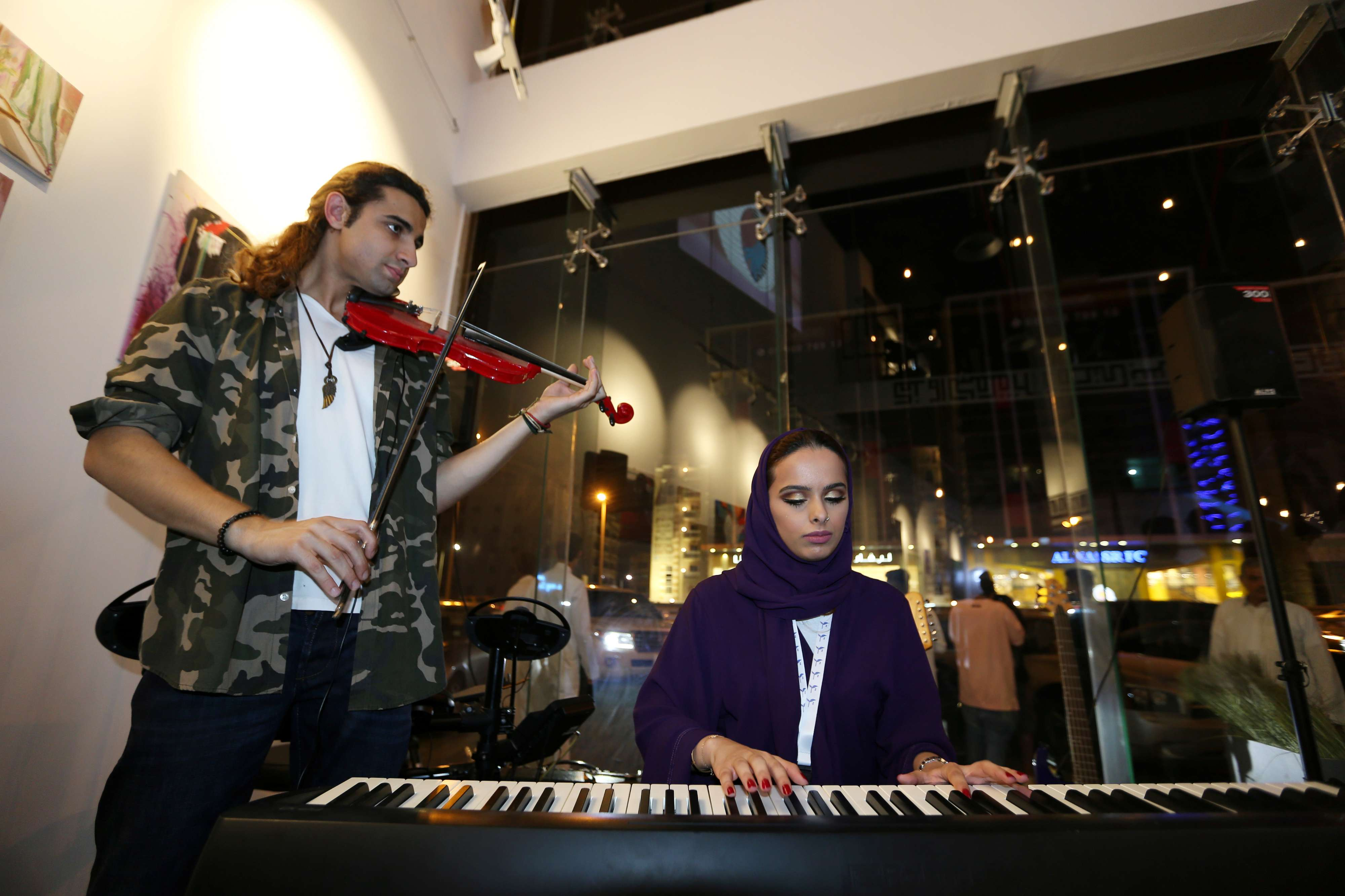 Cultural rebirth. Saudi female musician Lojain Sami (R) plays piano with Zaki Elnonoi, on violin, at a local musical themed cafe Lojain Alkhursani in Khobar, July 2.(Reuters)